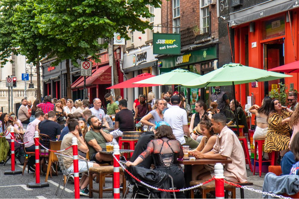Dublin crowds outside street 66 bar for drinks and outdoor dining on Parliament Street during weekend pedestrianization.