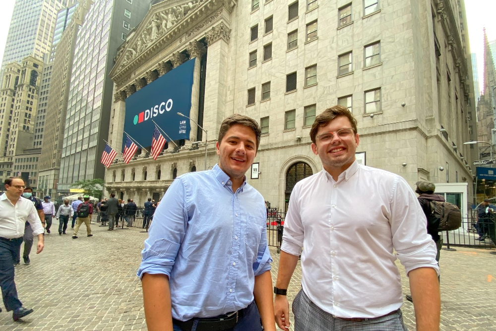 Two young men in front of the New York Stock Exchange.