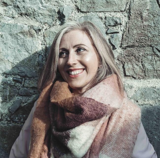Blonde woman wearing a scarf.