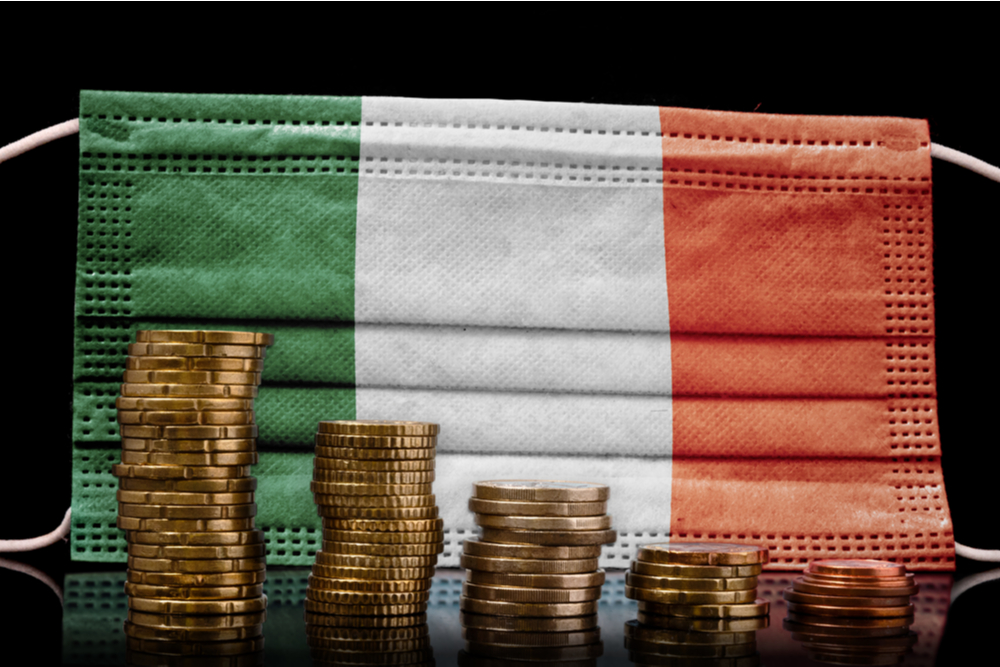 A surgical mask with the flag of Ireland behind some descending stacks of various coins.