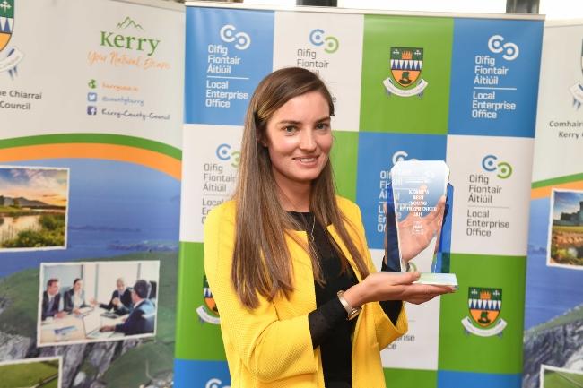 Brunette woman in yellow coat holding an award.