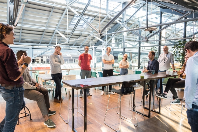 Group of people standing around a table.