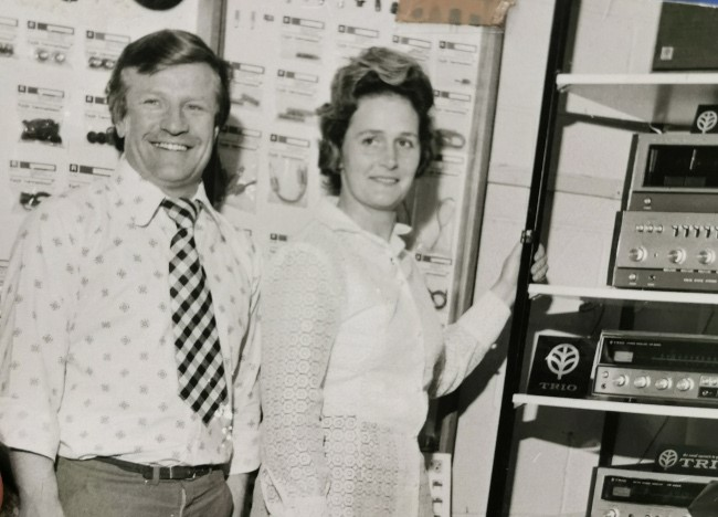 Man and his wife standing beside technology in the 1960s.