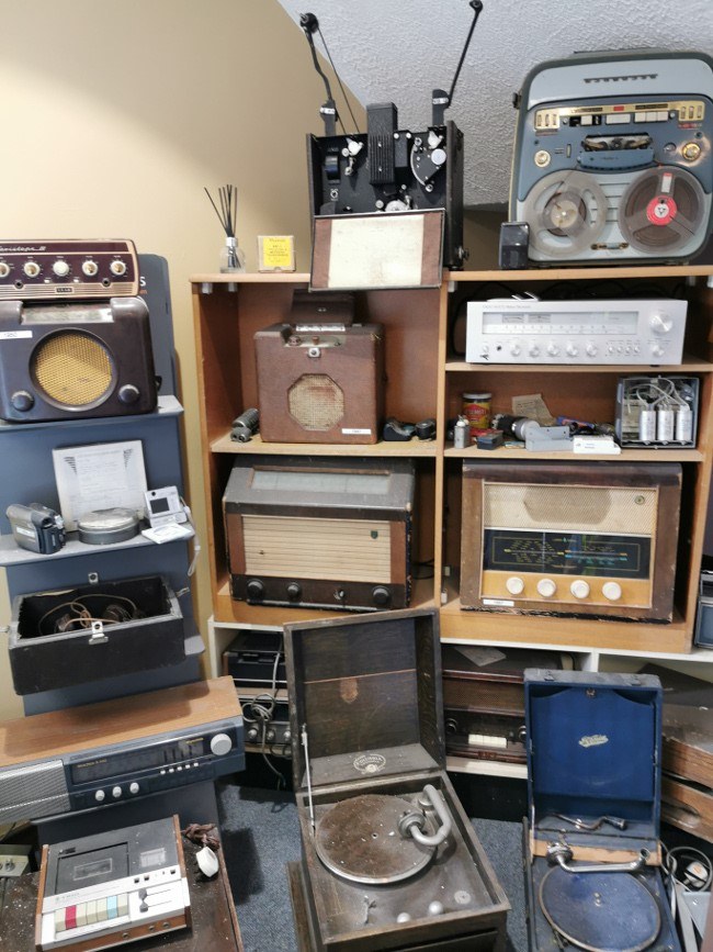 A jumble of old AV equipment including radios and record players.