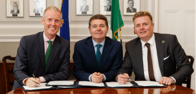 Three men in suits sign an agreement.