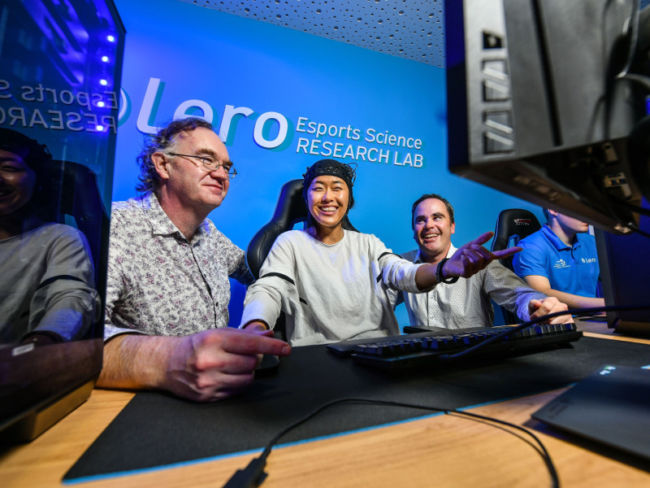 Two men and a woman playing video games.