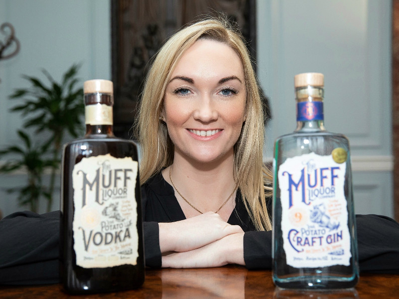 Blonde-haired woman stands in between a bottle of Irish gin and vodka.