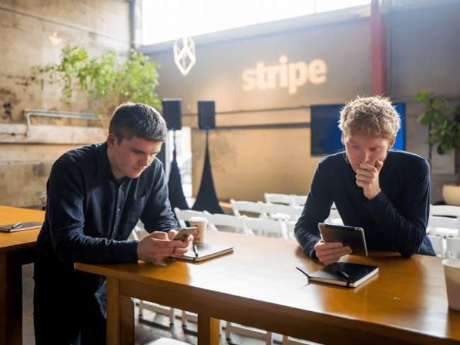 Two young men using electronic devices.