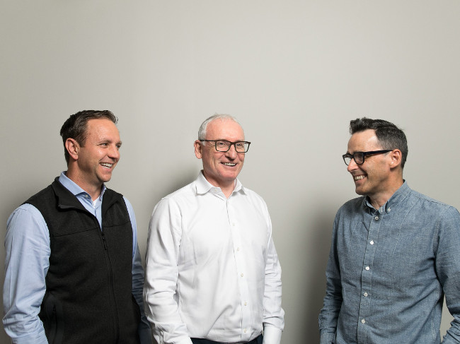 Three men smiling in front of a grey background.