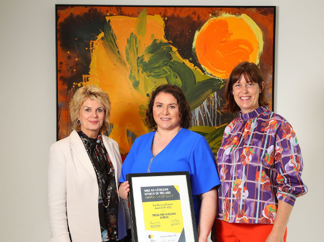 Three women holding a certificate standing in front of a colourful painting.