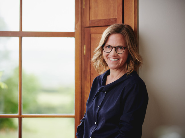 Woman with dark blonde hair and glasses smiling beside window.