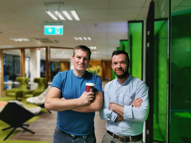 Two men standing with arms folded in a tech company.