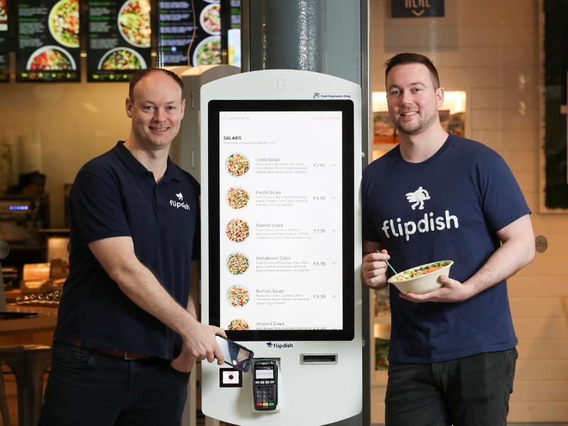 Two men in navy t-shirts either side of a digital kiosk for ordering food.