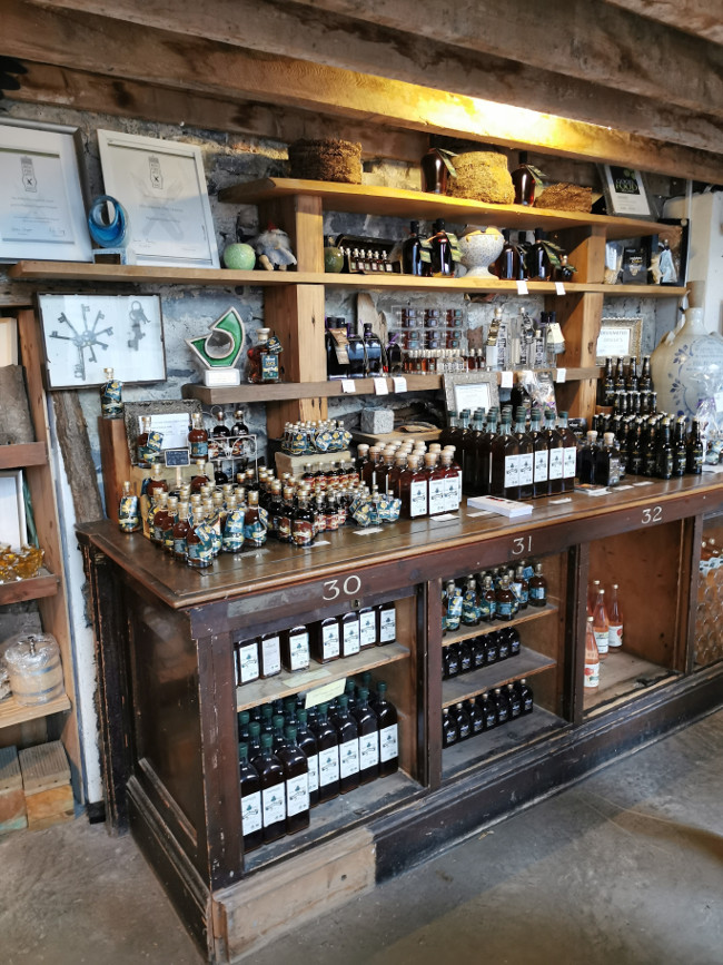 Cabinet of goods produced by Highbank Orchards including gins, ciders and syrups.