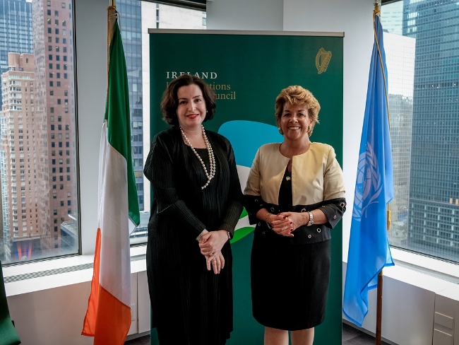 Two women standing in front of an Irish and a UN flag in New York city.