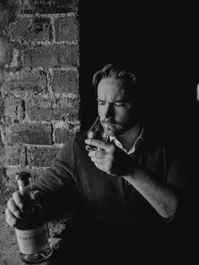 Man with beard sniffing at a glass of whiskey.